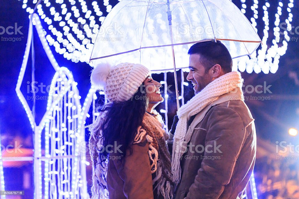 Couple standing face to face under umbrella at night stock photo