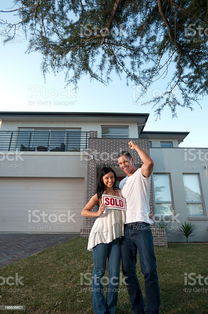 Couple standing in front of a house with sold sign royalty-free stock photo
