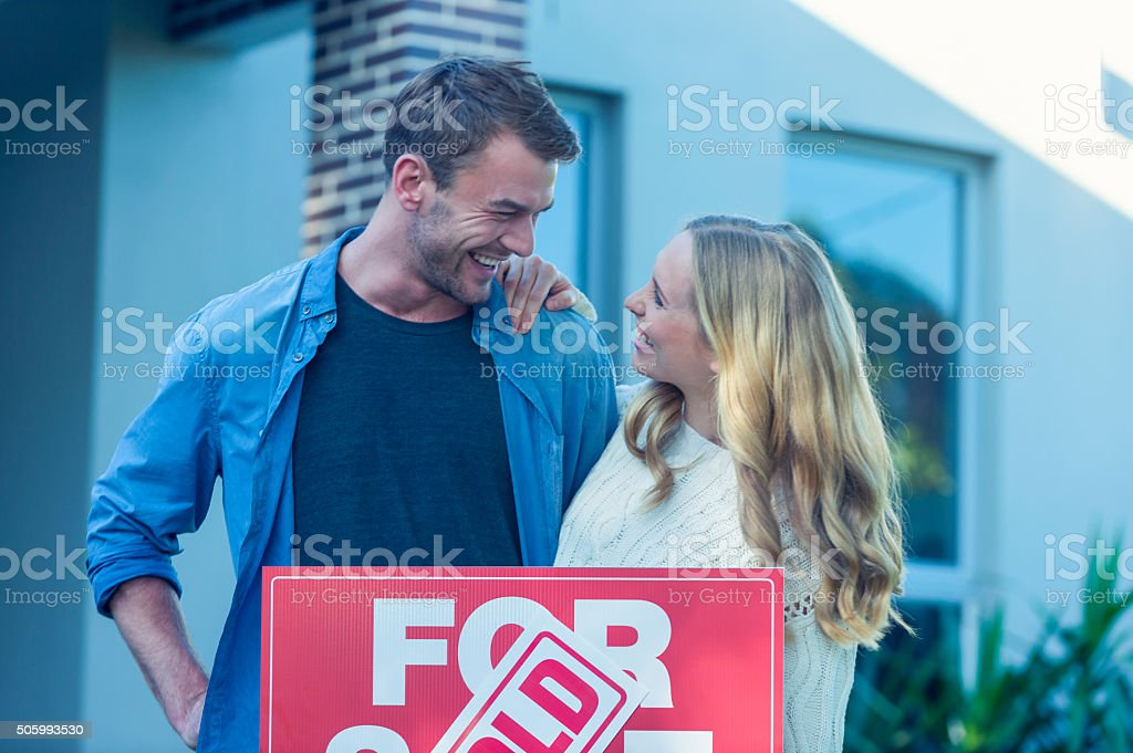 Couple standing in front of a new home stock photo
