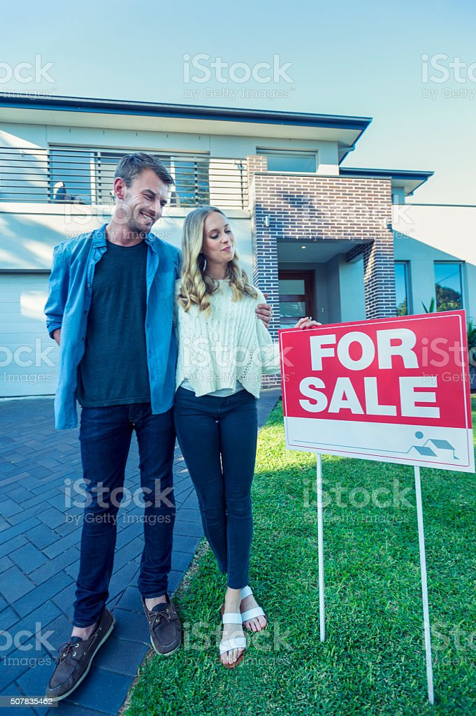 Couple standing in front of a new home. stock photo