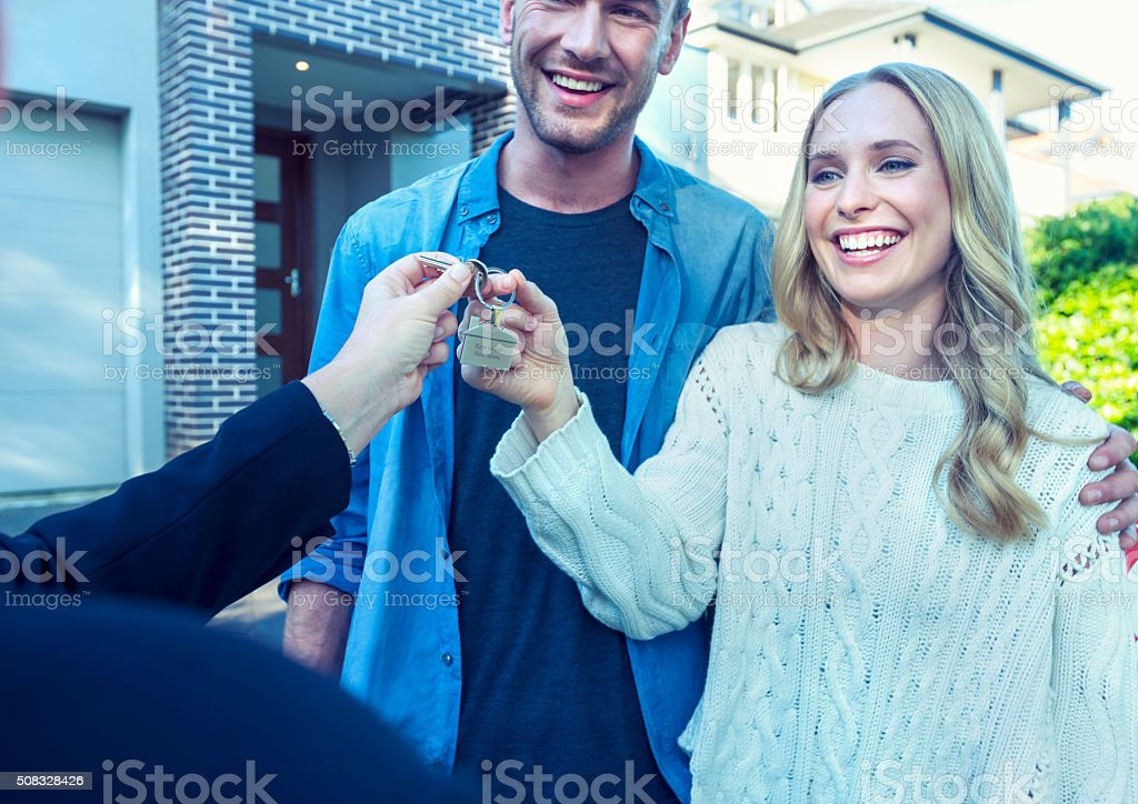 Couple standing in front of a new home with agent. stock photo