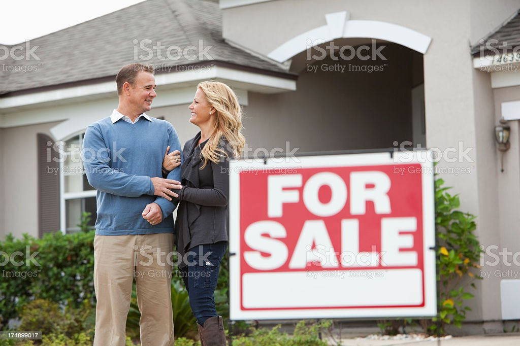 Couple standing in front of house for sale stock photo