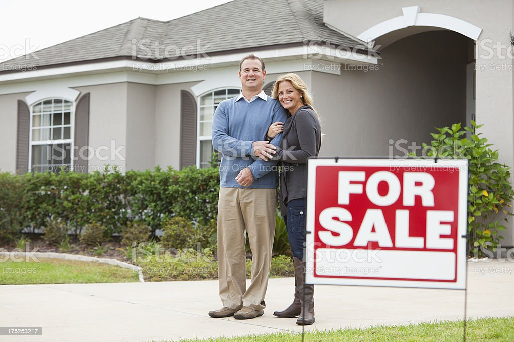 Couple standing in front of house for sale royalty-free stock photo