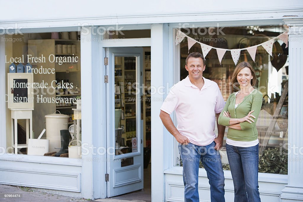 Couple standing in front of organic food store stock photo