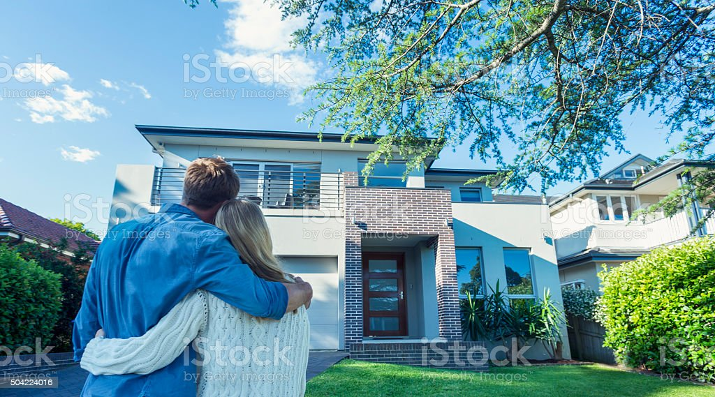 Couple standing in front of their new home. They are both wearing...