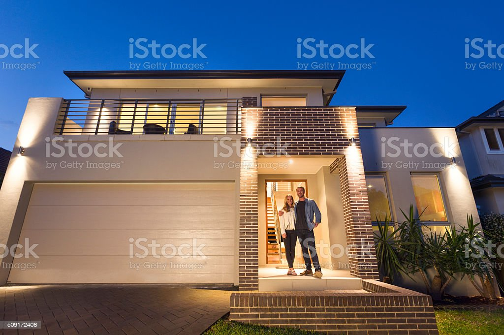 Couple standing in front of their new home stock photo