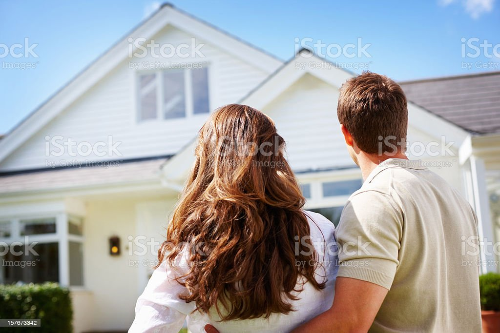 Couple standing in front of their new house stock photo