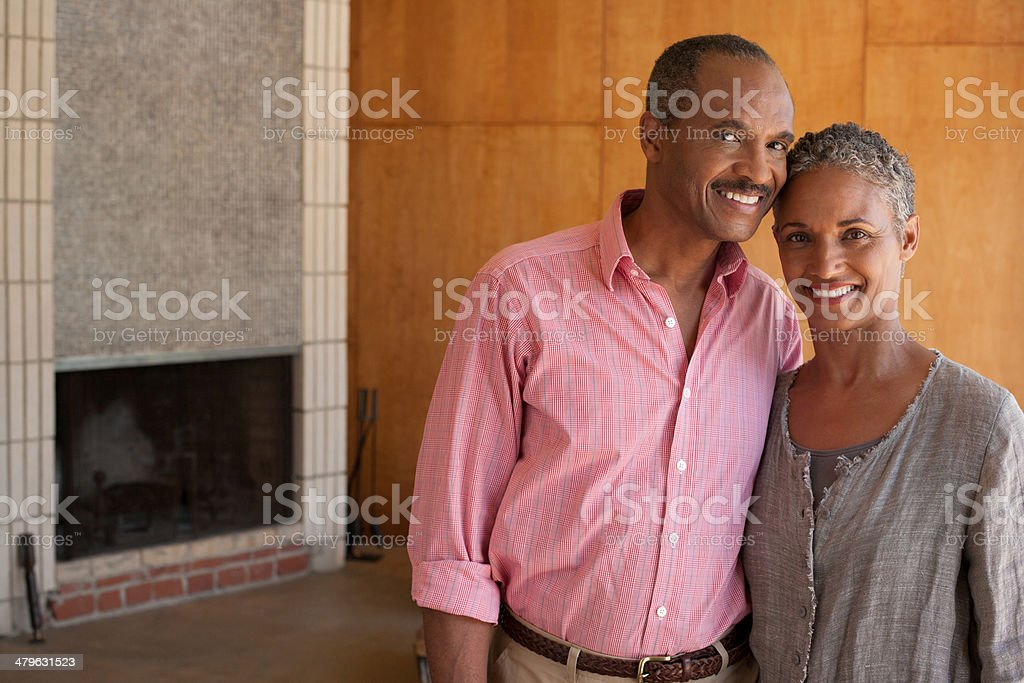 Couple standing in modern home near fireplace stock photo
