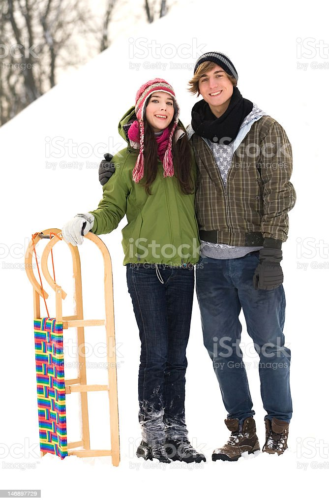 Couple standing in snow by sled royalty-free stock photo