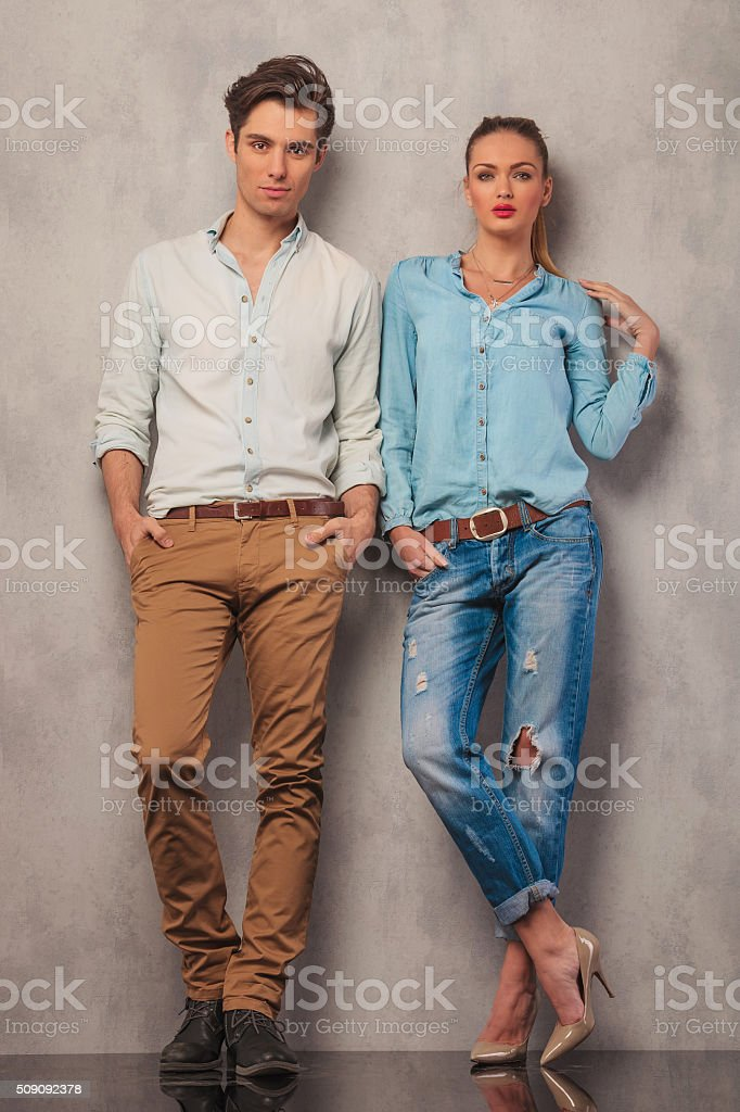 couple standing in studio posing with hands in pockets stock photo