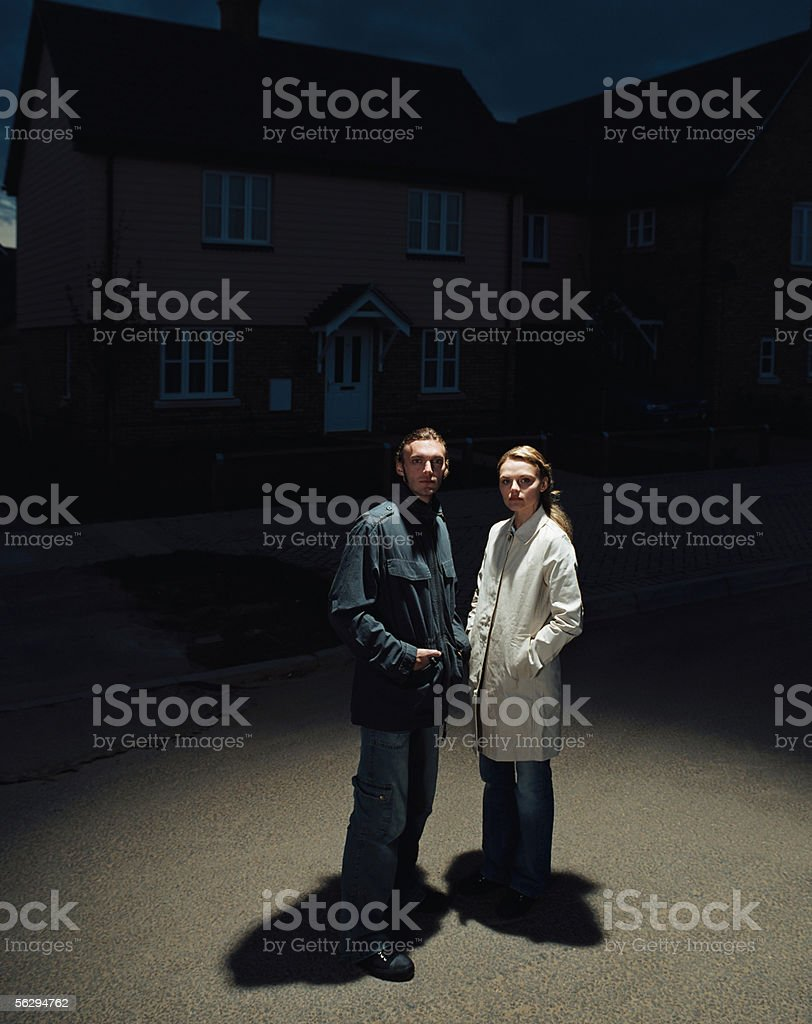 Couple standing in the street at night stock photo