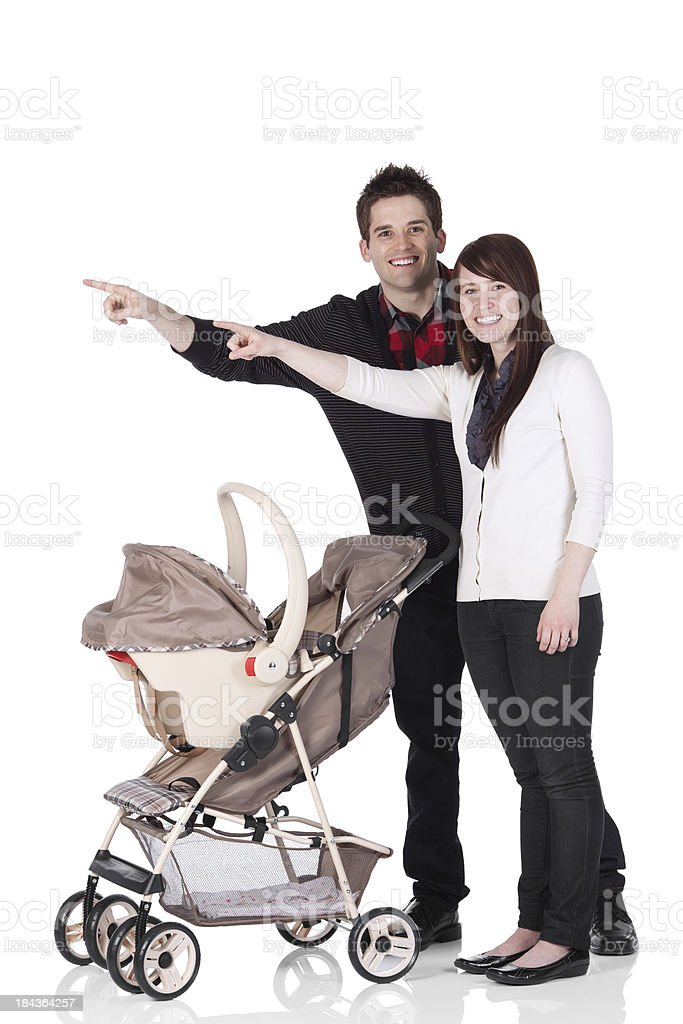 Couple standing near a baby carrier and pointing stock photo