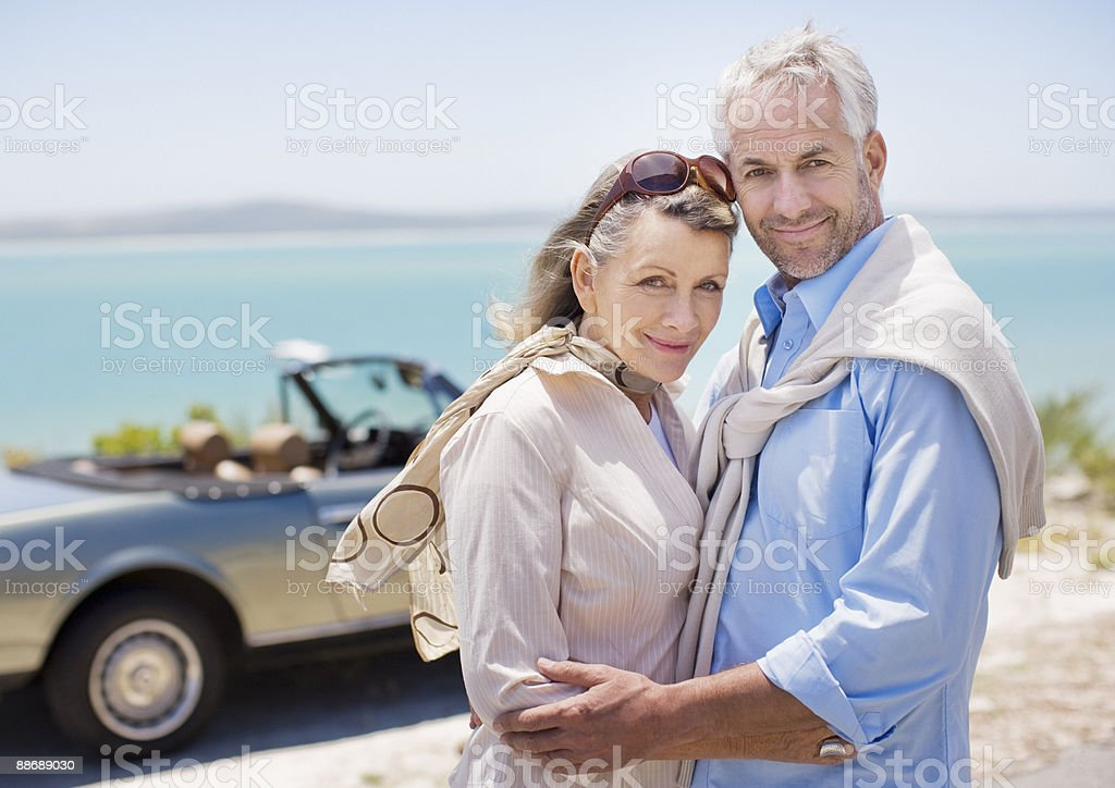 Couple standing near convertible royalty-free stock photo