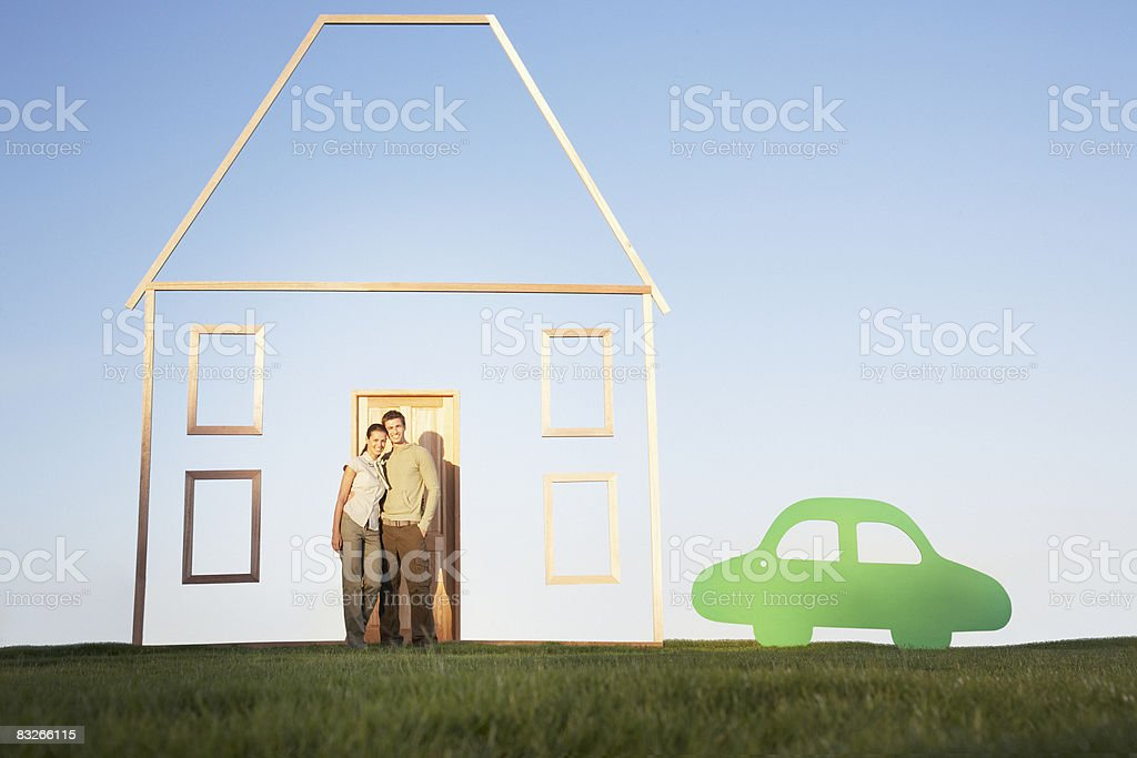 Couple standing next to vertical house outline and car cutout stock photo
