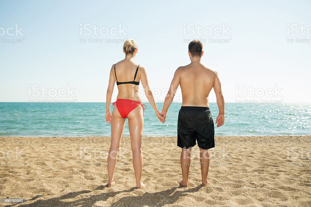Couple standing on a beach stock photo