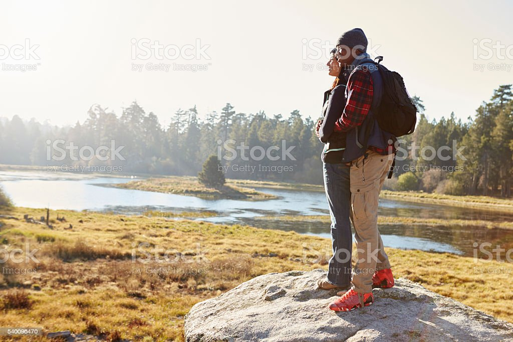Couple standing on a rock in countryside, admiring the view stock photo