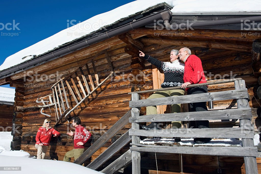 Couple standing on balcony another couple standing next to hut stock photo