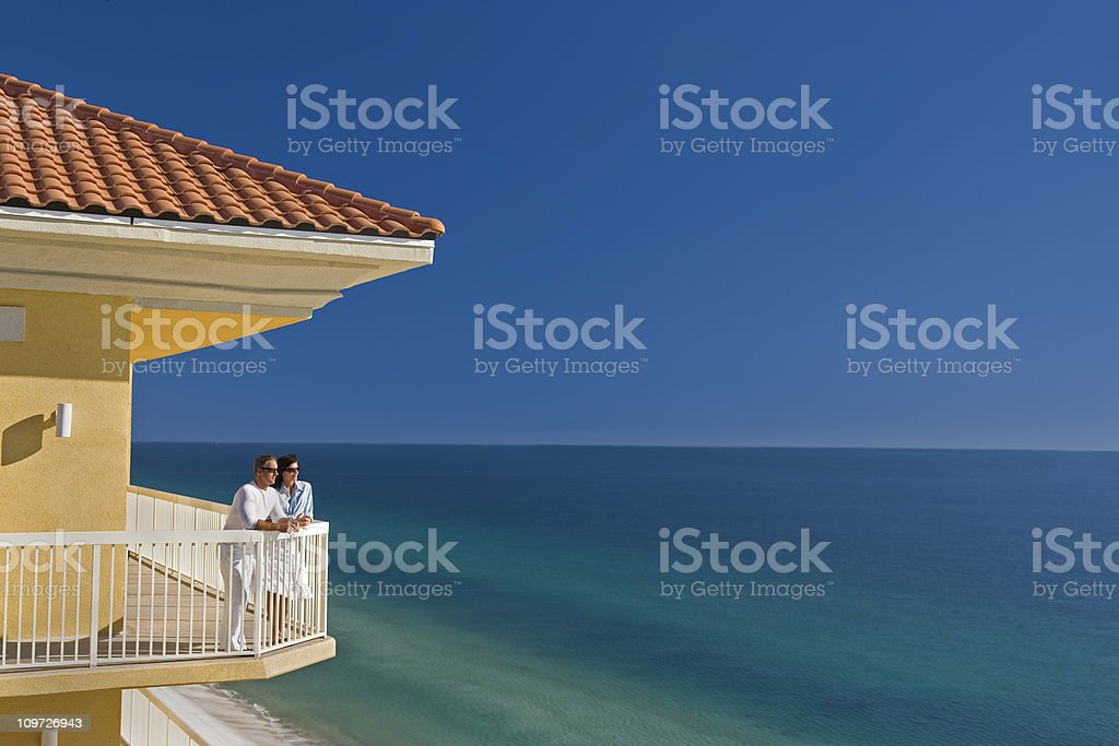 Couple Standing on Balcony Looking At The Ocean stock photo