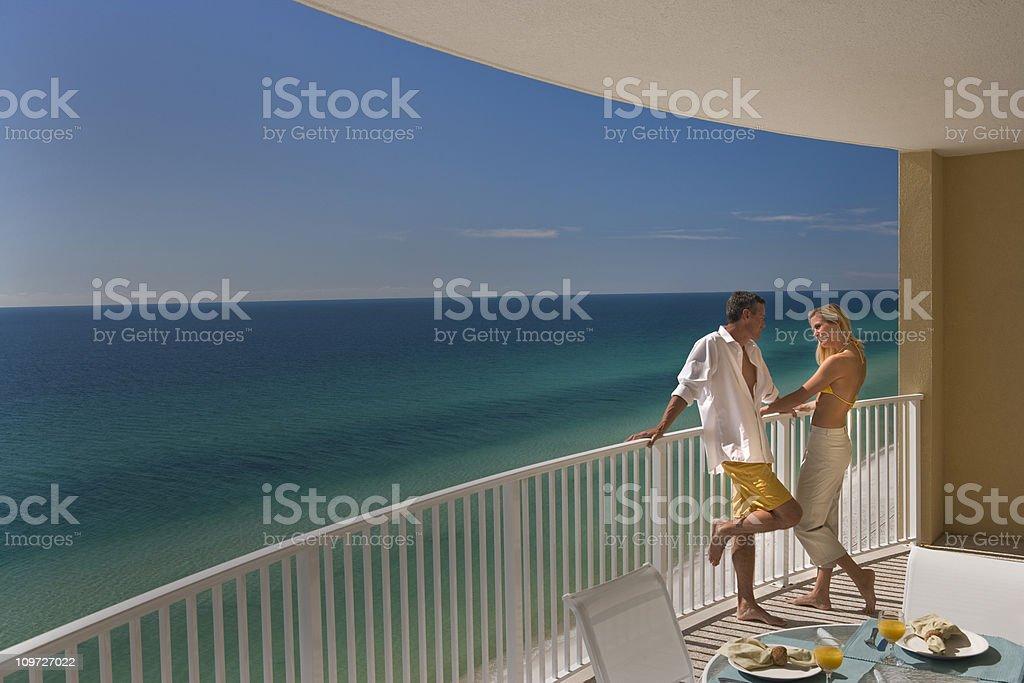 Couple Standing On Balcony Overlooking Gulf of Mexico stock photo