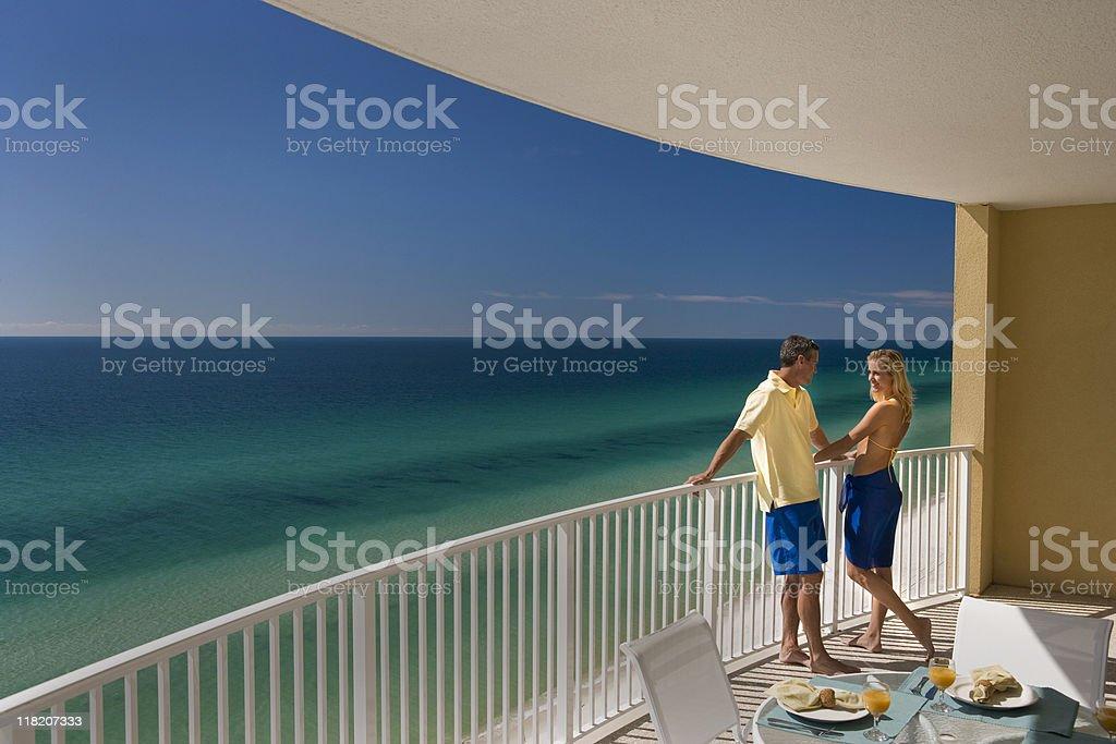 Couple Standing On Balcony Overlooking Ocean royalty-free stock photo