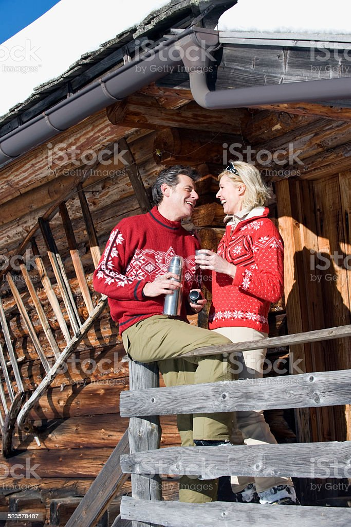 Couple standing on deck of log cabin, holding thermos flask stock photo