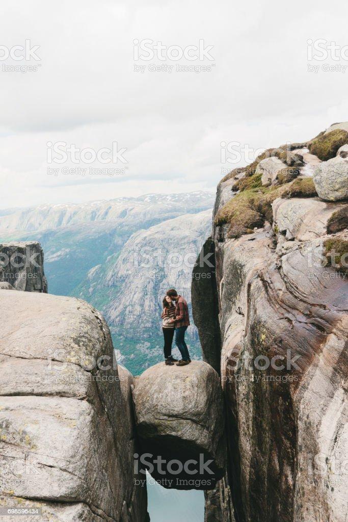 Couple standing on Kjeragbolten stock photo