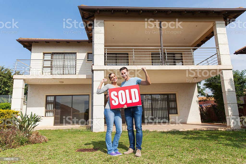 couple standing outside their house stock photo