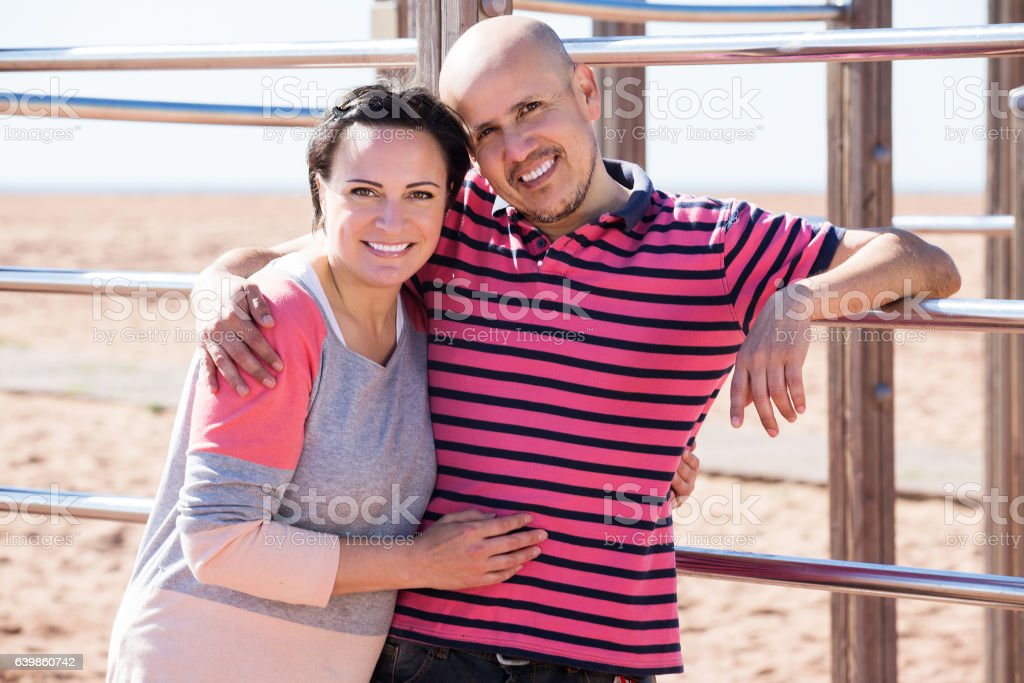 Couple standing to wall bars stock photo