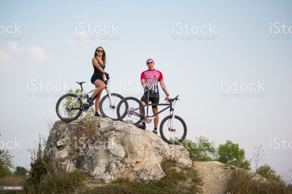 Couple standing with bicycles on the rock under evening sky stock photo