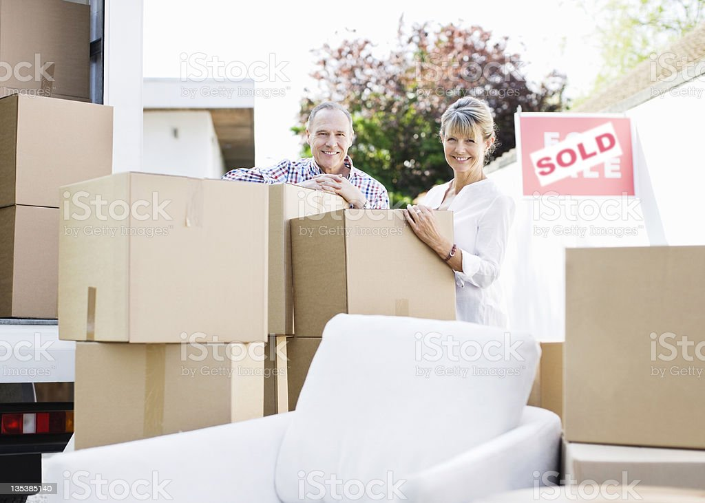 Couple standing with boxes and moving van royalty-free stock photo