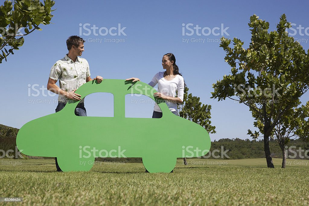 Couple standing with cutout car stock photo