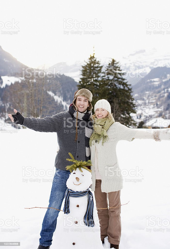 Couple standing with snowman royalty-free stock photo