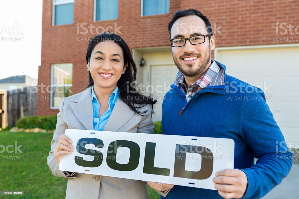 Couple stands in front of new home holding 'sold' sign stock photo