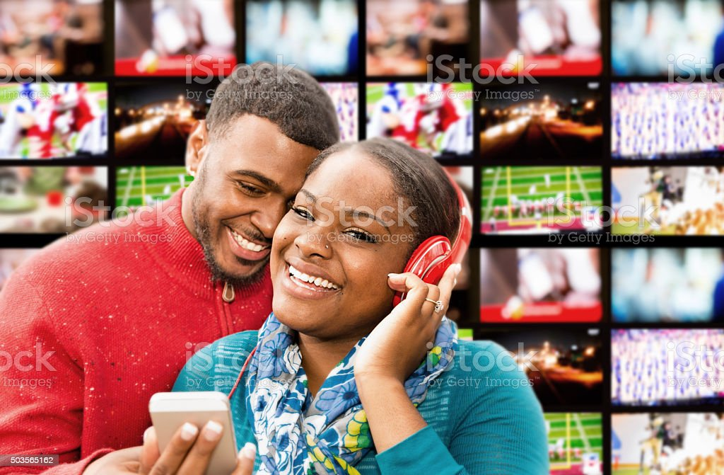 Couple stands in front of TVs at electronics store. stock photo