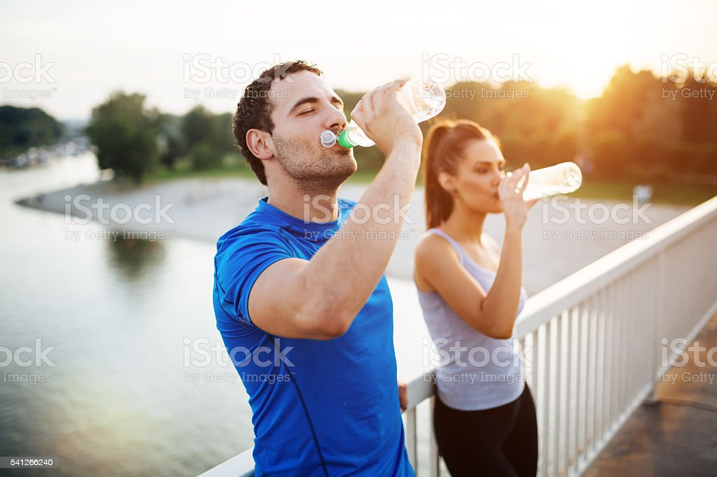 Couple staying hydrated stock photo