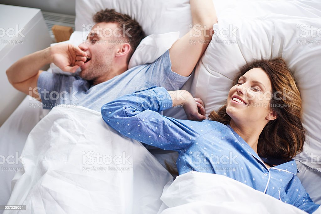 Couple stretching and yawning in bed stock photo