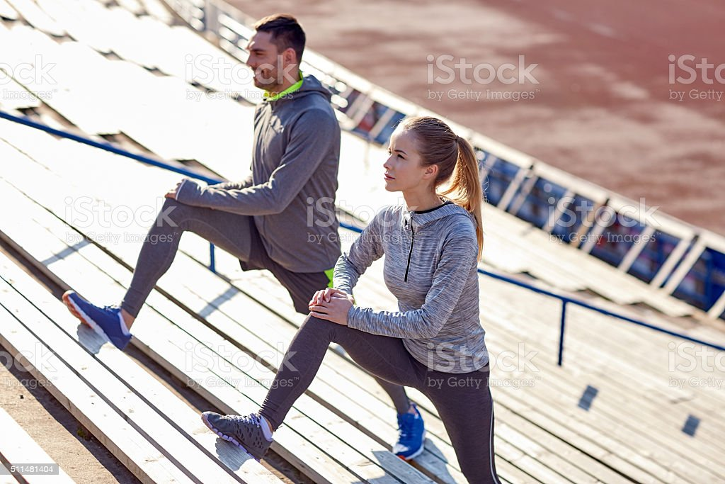 couple stretching leg on stands of stadium stock photo