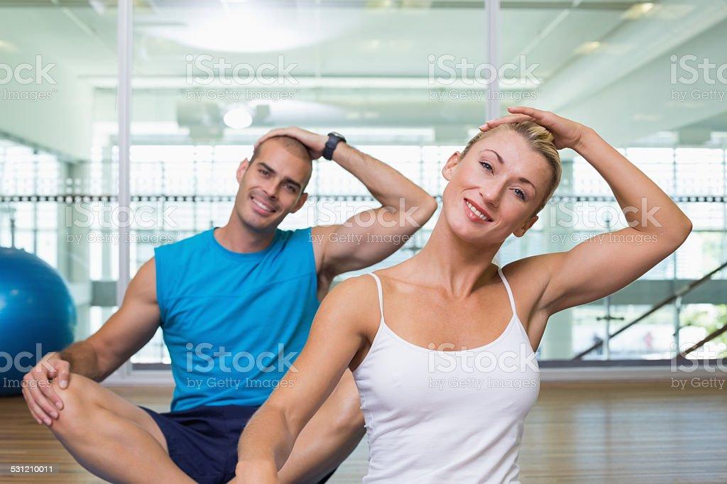 Couple stretching necks in yoga class stock photo