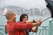 Couple struggling with umbrella in bad weather / rain, HongKong