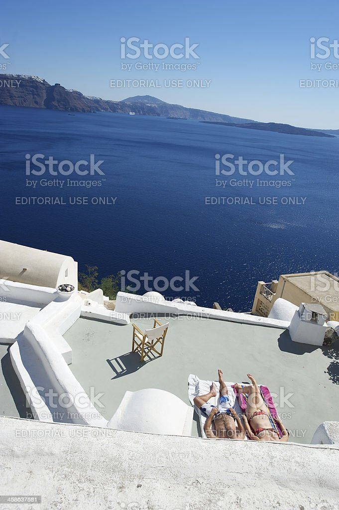 Couple Sunbathes on Bright Santorini Balcony royalty-free stock photo