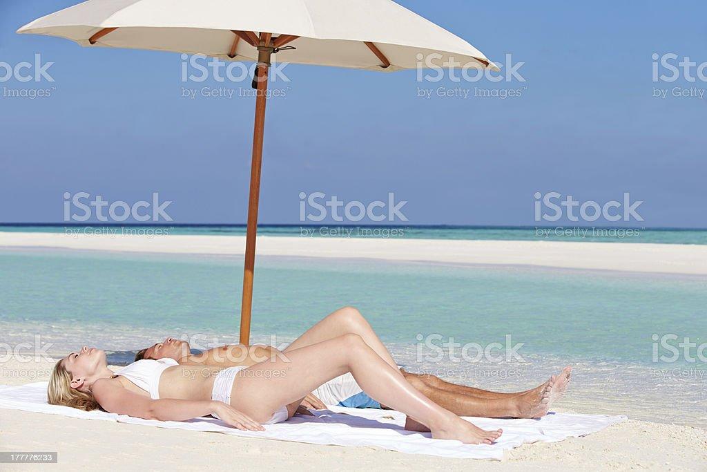 Couple Sunbathing On Beautiful Beach Holiday royalty-free stock photo