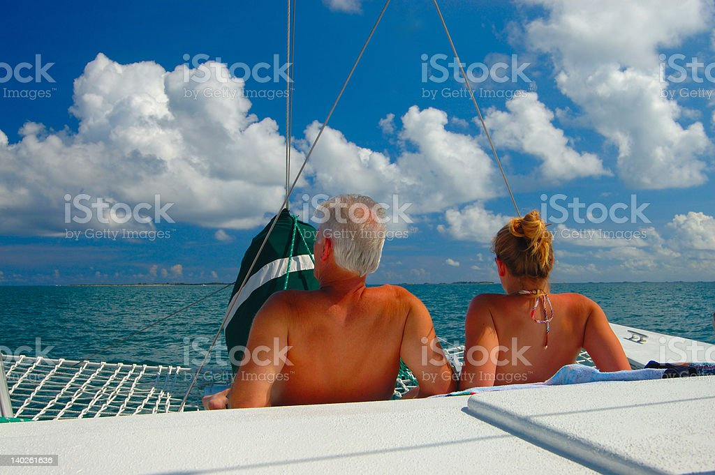 couple sunbathing on sail boat off Caribbean sea royalty-free stock photo