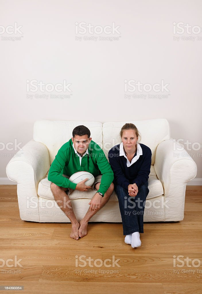 Couple Supporting Opposing Rugby Teams Concentrating On A Tense Match stock photo