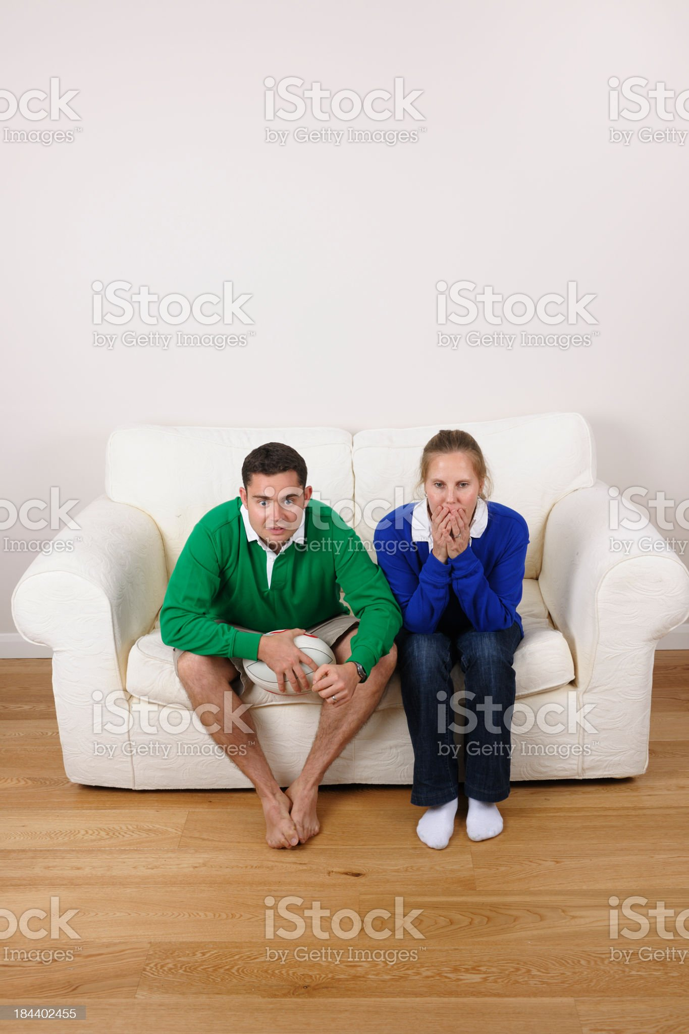 Couple Supporting Opposing Rugby Teams Watching A Tense Televised Match royalty-free stock photo