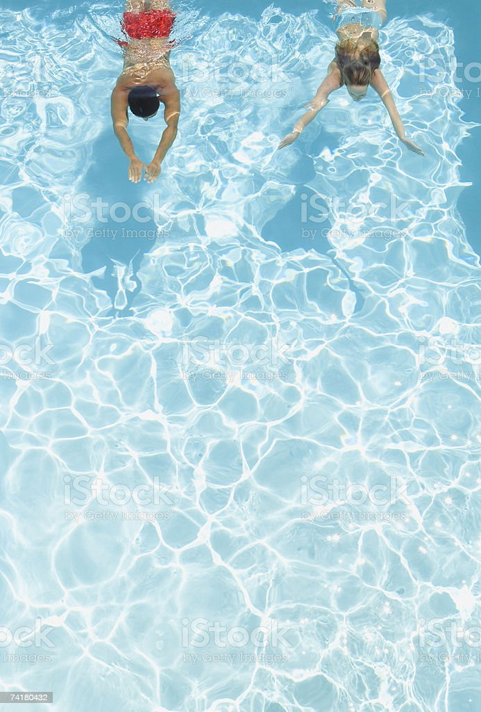 Couple swimming in pool stock photo