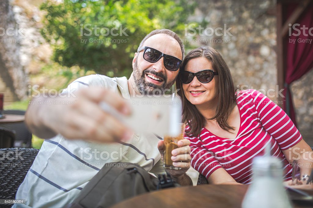 Couple take a selfie in coffee shop stock photo