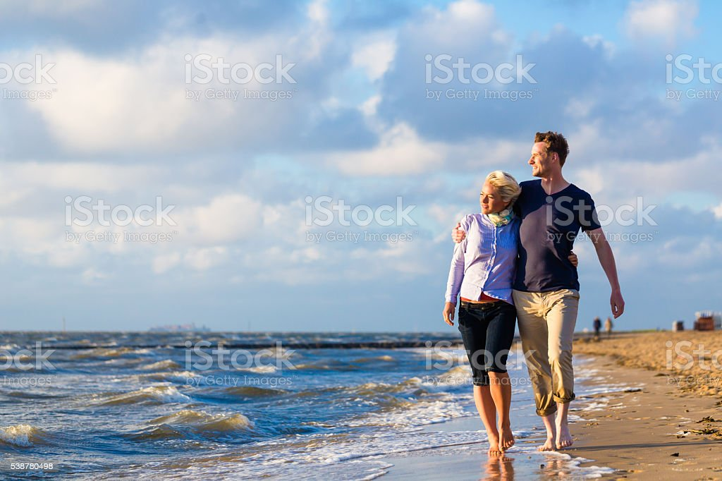 Couple take a walk at German north sea beach stock photo