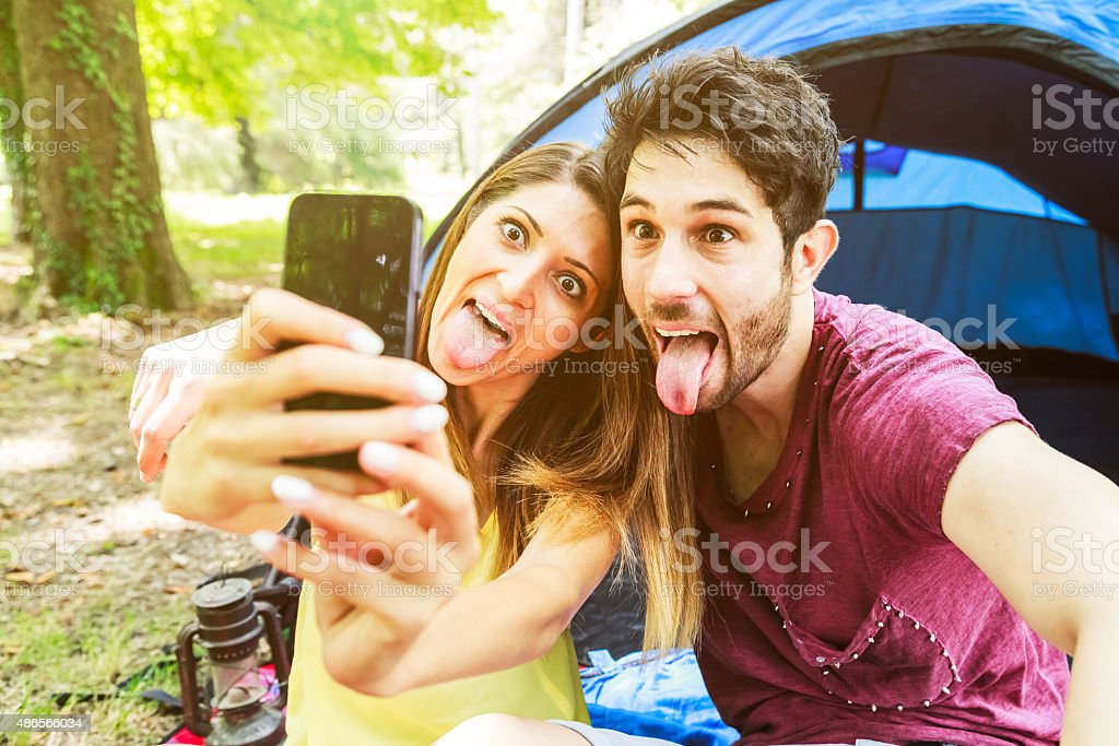 Couple takes a selfie in tents at the campsite stock photo