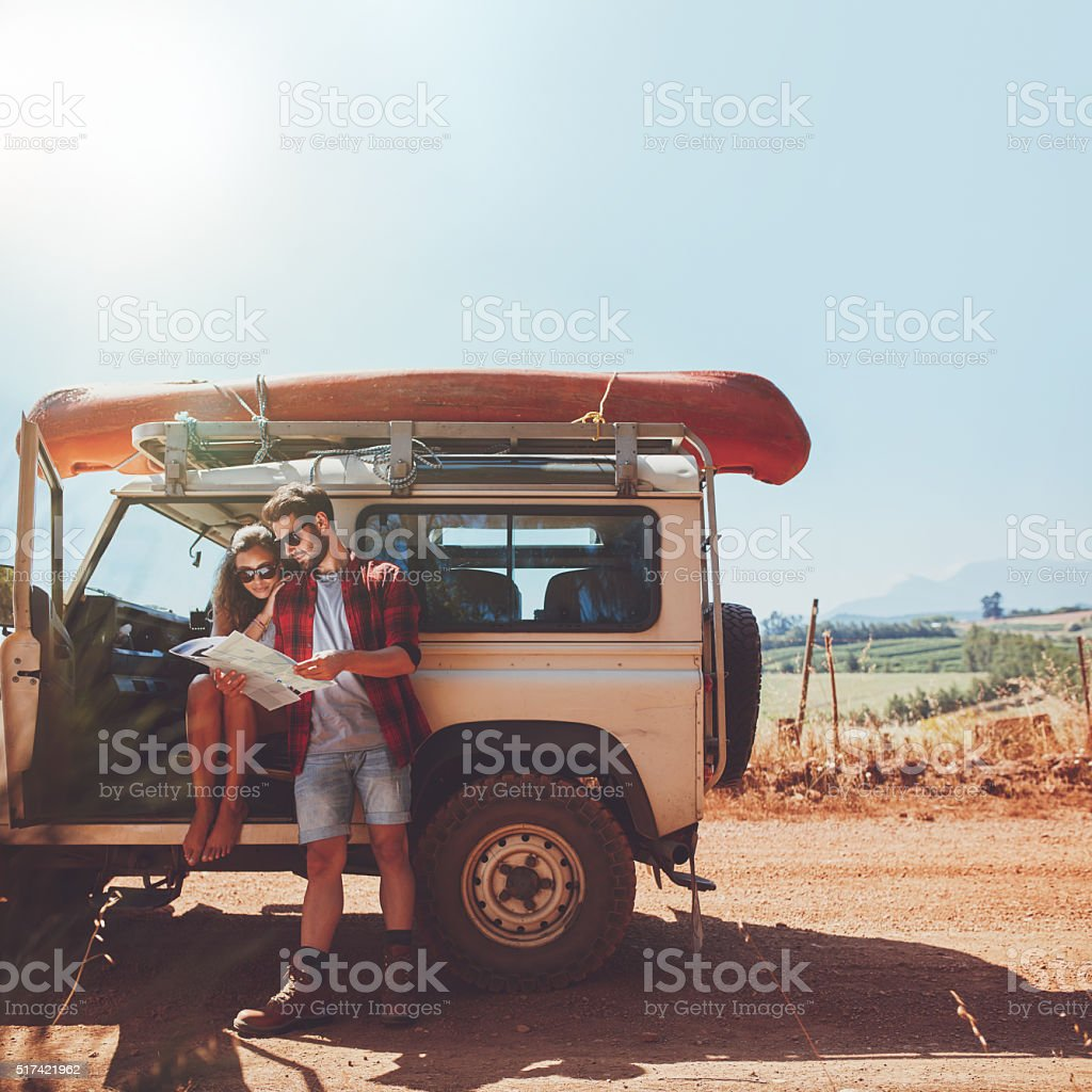 Couple taking a break to look at map on roadtrip stock photo