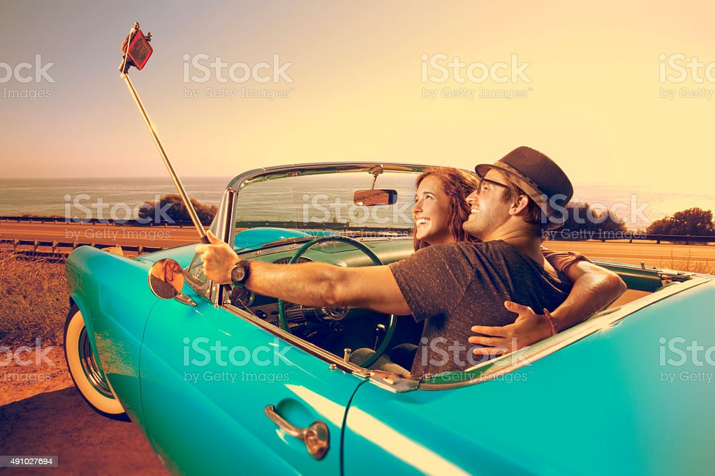 Couple Taking a photo with  a selfie stick in a Convertible stock photo